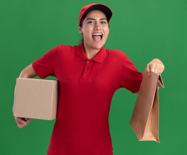 Радостная молодая доставщица в униформе и кепке держит коробку с бумажным пакетом продуктов, изолированным на зеленой стене