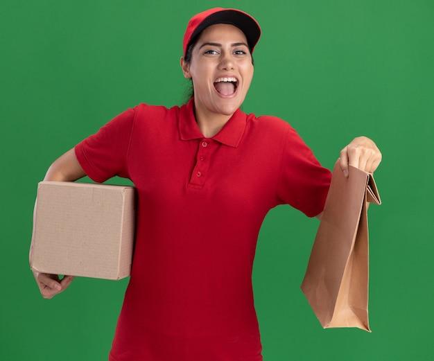 Giovane ragazza allegra di consegna che indossa l'uniforme e la scatola della tenuta del cappuccio con il pacchetto di cibo di carta isolato sulla parete verde