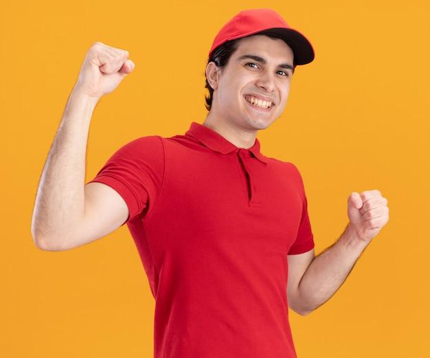 Gioioso giovane fattorino in uniforme blu e berretto che guarda davanti facendo sì gesto isolato sulla parete arancione