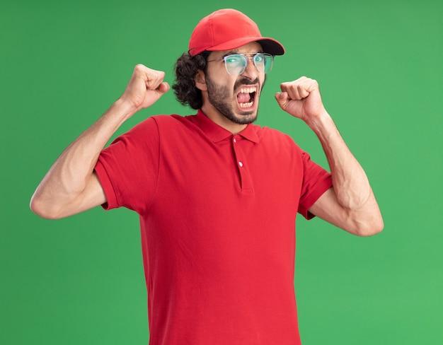 빨간 제복을 입은 즐거운 젊은 배달원과 녹색 벽에 격리된 예 제스처를 하는 앞을 바라보는 안경을 쓴 모자