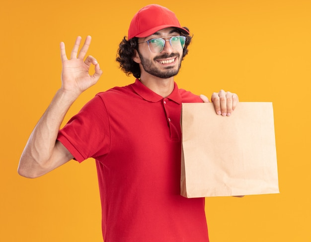 Joyful young delivery man in red uniform and cap wearing glasses holding paper package looking at front doing ok sign isolated on orange wall