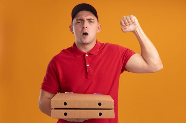 オレンジ色の壁にイエスのジェスチャーを示すピザの箱を持った帽子をかぶった制服を着たうれしそうな若い配達人