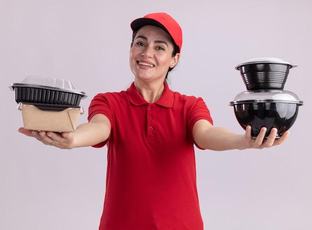紙の食品パッケージと食品容器を伸ばして制服とキャップでうれしそうな若い配達の女性