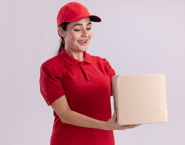 Joyful young delivery woman in uniform and cap holding and looking at cardbox isolated on white wall
