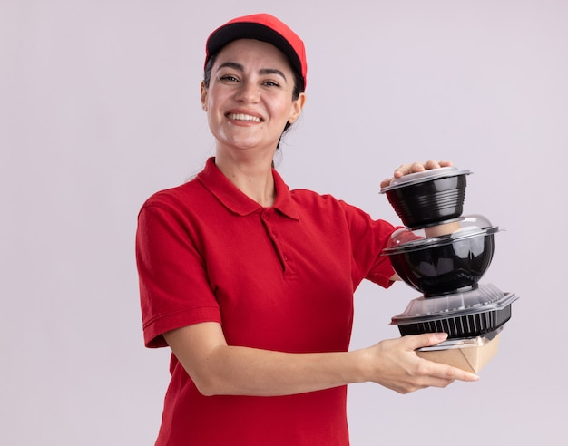 Joyful young delivery woman in uniform and cap holding paper food package and food containers  isolated on white wall