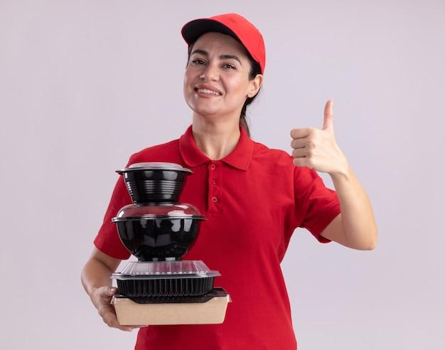 Gioiosa giovane donna delle consegne in uniforme e cappuccio che tiene in mano un pacchetto di alimenti di carta e contenitori per alimenti che mostrano pollice in su isolato su muro bianco