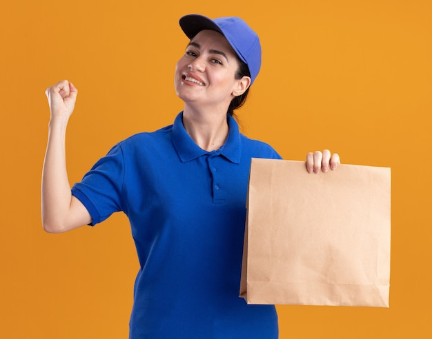 Gioiosa giovane donna delle consegne in uniforme e cappuccio che tiene un pacchetto di carta guardando davanti facendo un gesto forte isolato sulla parete arancione