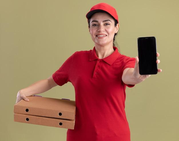 Gioiosa giovane donna delle consegne in uniforme e berretto che tiene in mano i pacchetti di pizza che allungano il telefono cellulare