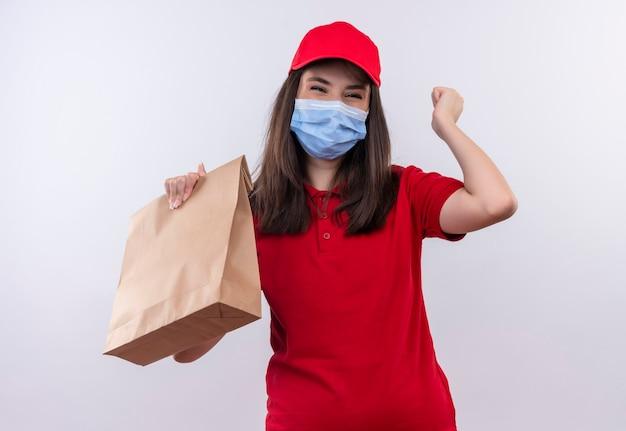 Gioiosa giovane donna di consegna che indossa la maglietta rossa in berretto rosso che tiene un pacchetto sulla parete bianca isolata