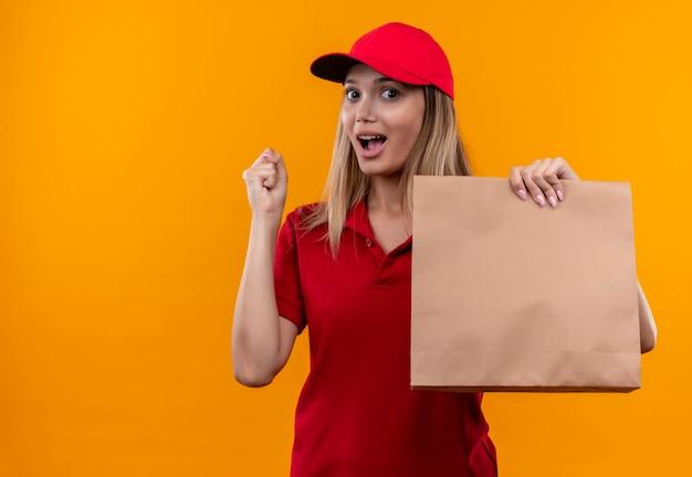 Радостная молодая доставщица в красной форме и кепке держит бумажный пакет и показывает жест