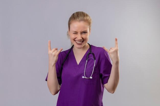 紫色の医療用ガウンと聴診器を身に着けているうれしそうな若い医者は、孤立した白い壁に両手でヤギのジェスチャーを示しています