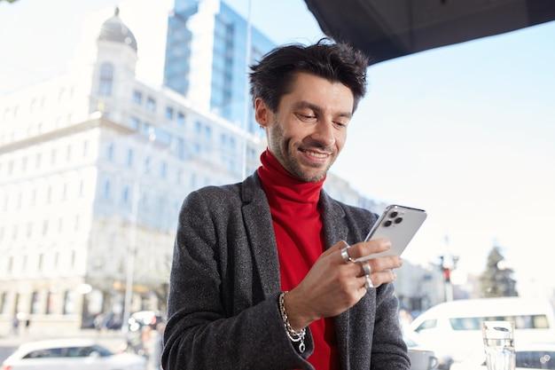 Gioioso giovane ed elegante ragazzo barbuto dai capelli scuri che tiene il telefono cellulare e sorride volentieri mentre controlla i suoi social network, in piedi sopra il fondo urbano