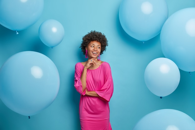 Joyful young elegant woman in pink dress enjoys birthday party or other celebration, looks aside with happy expression, poses against balloons on blue wall, waits for special event in life