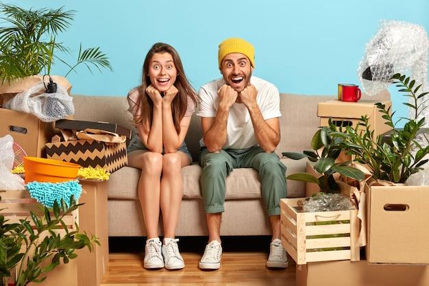 Радостная молодая семейная пара приятно удовлетворена, держится за подбородки, одета в повседневную одежду, окружена множеством личных вещей в коробках
