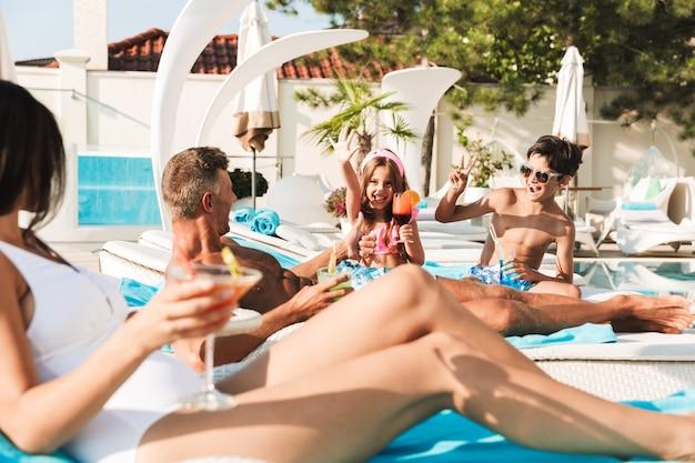 Радостная молодая семья весело вместе в бассейне