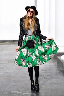 Gioiosa giovane donna alla moda in lunga gonna verde, sui tacchi che camminano sulla strada nella soleggiata primavera. capelli lunghi, cappello, occhiali da sole, sorridere alla telecamera, godersi il tempo soleggiato, modello elegante