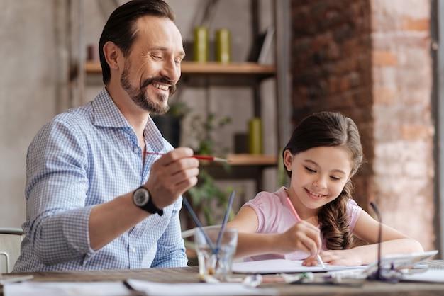 ブラシを持っているうれしそうな若い父親は、写真にいくつかのストロークを適用する準備ができているので、彼のかわいい小さな娘が写真を仕上げるのを手伝っています
