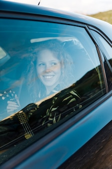 Joyful young female in car