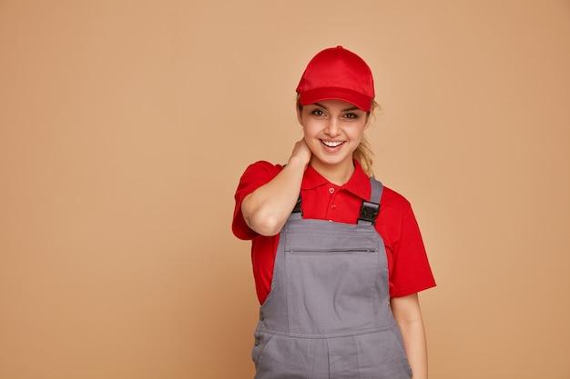 Gioiosa giovane operaio edile femminile che indossa l'uniforme e cappuccio tenendo la mano sul collo