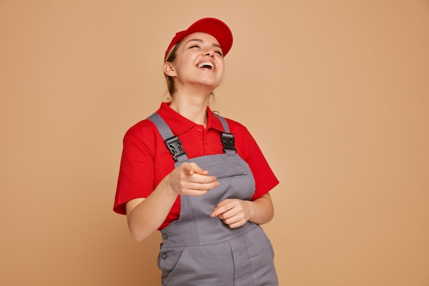 Gioioso giovane operaio edile femminile che indossa uniformi e berretto alzando lo sguardo rivolto verso la telecamera ridendo