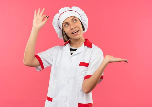 Gioiosa giovane donna cuoca in uniforme da chef facendo segno ok e mostrando la mano vuota guardando il lato isolato sul rosa