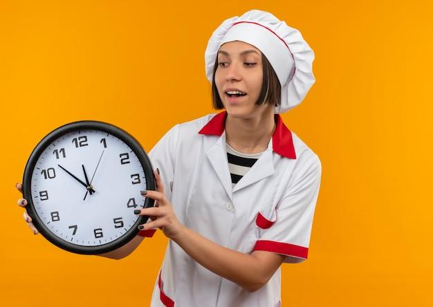 Gioioso giovane cuoco femminile in uniforme del cuoco unico che tiene e che guarda l'orologio isolato sull'arancio