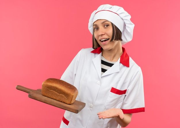 Joyful young female cook in chef uniform holding and pointing with hand at cutting board with bread on it isolated on pink