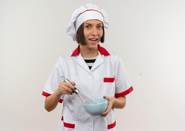 Gioioso giovane cuoco femminile in uniforme del cuoco unico che tiene frusta e ciotola isolato su bianco