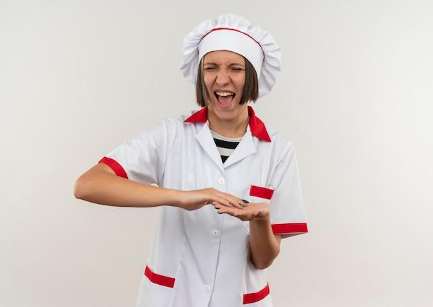 Gioioso giovane cuoco femminile in uniforme del cuoco unico che tiene le mani insieme agli occhi chiusi isolati su bianco