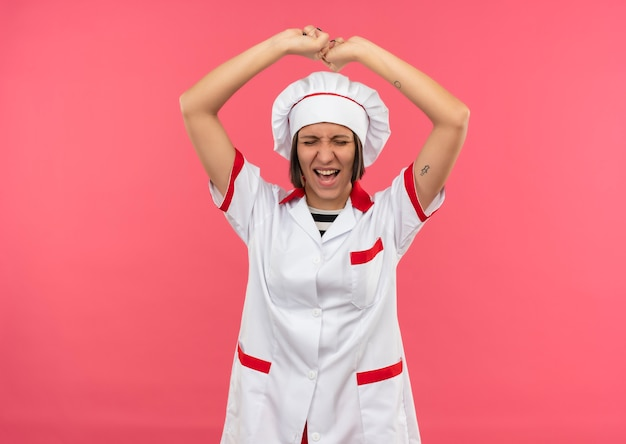 Joyful young female cook in chef uniform raising fists with closed eyes isolated on pink