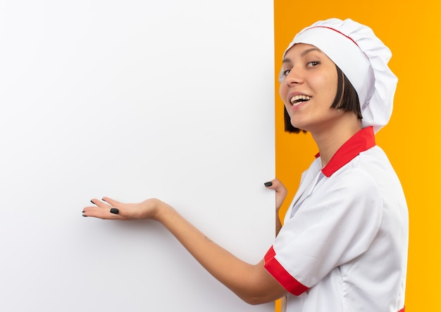 Gioioso giovane cuoco femminile in uniforme da chef in piedi vicino a muro bianco che tiene e che indica con la mano isolato sull'arancio
