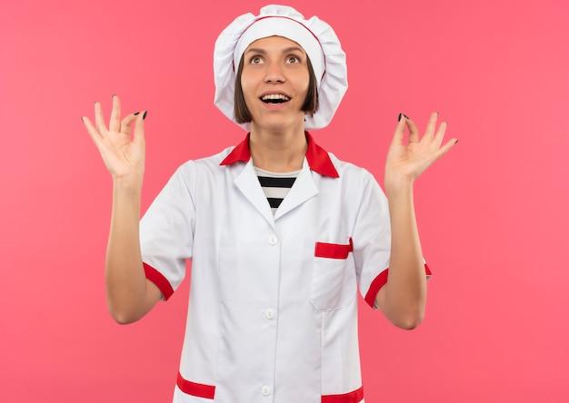 요리사 유니폼에 즐거운 젊은 여성 요리사는 분홍색에 고립 된 찾고 확인 표시를하고