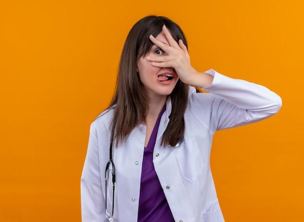 聴診器と医療ローブのうれしそうな若い女性医師は彼女の舌を突き出し、コピースペースで孤立したオレンジ色の背景に彼女の手の指を通して見ます