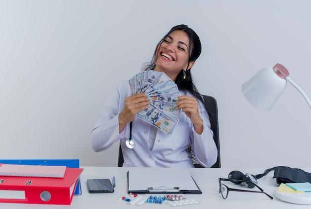 의료 가운과 청진기를 입고 즐거운 젊은 여성 의사가 고립 된 닫힌 눈으로 돈을 들고 의료 도구와 책상에 앉아