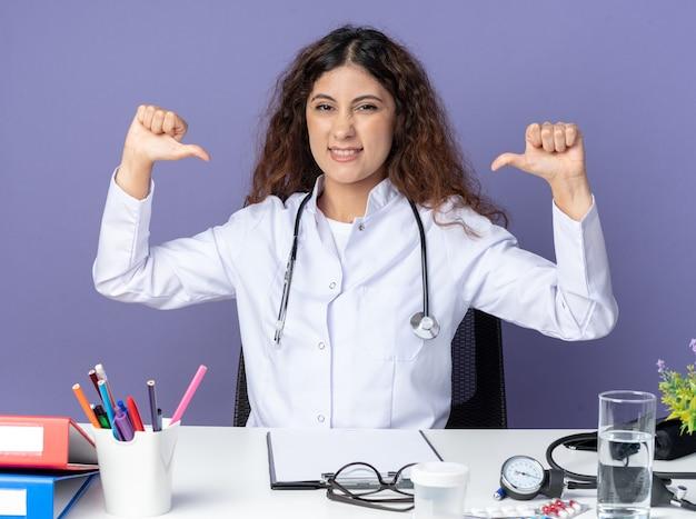 紫色の壁に隔離された自分自身を指している正面を見て医療ツールとテーブルに座って医療ローブと聴診器を身に着けているうれしそうな若い女性医師