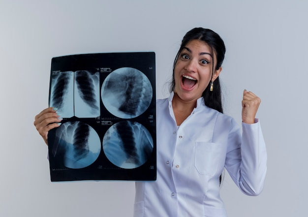 Joyful young female doctor wearing medical robe holding x-ray shot looking doing yes gesture isolated