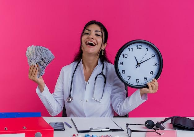 Gioioso giovane medico femminile che indossa abito medico e stetoscopio seduto alla scrivania con strumenti medici che tengono soldi e orologio isolato sulla parete rosa