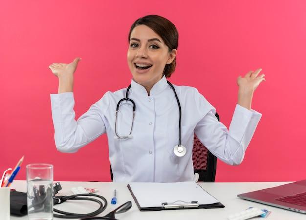 Gioioso giovane medico femminile che indossa abito medico e stetoscopio seduto alla scrivania con strumenti medici e computer portatile che mostra le mani vuote isolate sul muro rosa
