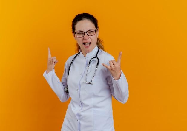 Gioioso giovane medico femminile che indossa abito medico e stetoscopio con gli occhiali che mostrano gesti di capra isolati