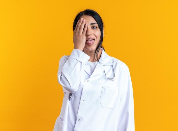 Gioiosa giovane dottoressa che indossa un abito medico con uno stetoscopio coperto l'occhio con la mano isolata sulla parete gialla