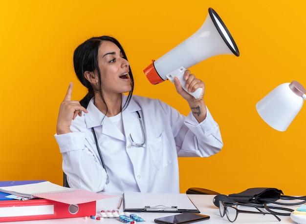청진 기 의료 가운을 입고 즐거운 젊은 여성 의사 의료 도구 테이블에 앉아 노란색 벽에 고립 된 스피커에 말한다