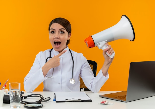Joyful young female doctor wearing medical robe with stethoscope sitting at desk work on computer with medical tools holding and points to loudspeaker on isolation yellow wall
