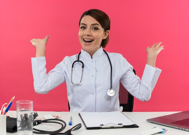 Joyful young female doctor wearing medical robe with stethoscope sitting at desk work on computer with medical tools spreads hands on isolated pink wall with copy space