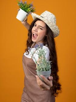 원예 모자를 쓰고 제복을 입은 즐거운 젊은 여성 정원사는 눈을 깜박이고 복사 공간이 오렌지 벽에 고립 된 화분을 보유하고 있습니다.