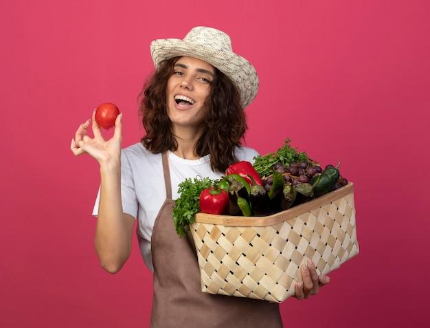 Gioioso giovane giardiniere femminile in uniforme che indossa cappello da giardinaggio tenendo il cesto di verdure con pomodoro isolato sul colore rosa