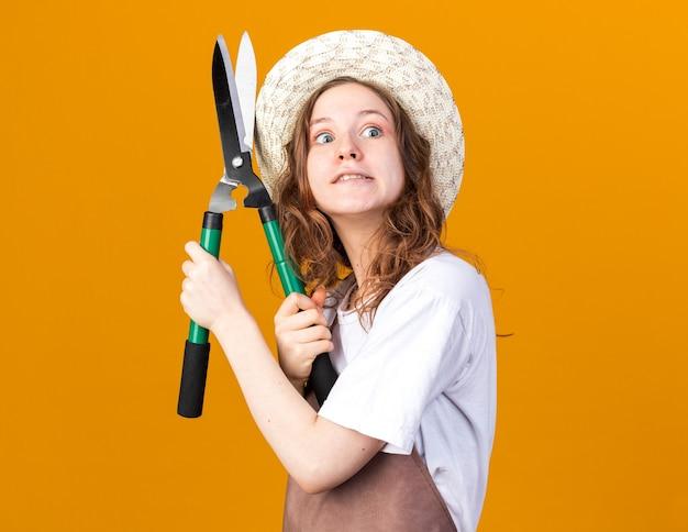 Gioiosa giovane giardiniere femmina che indossa cappello da giardinaggio tenendo la forbice da potatura isolata sulla parete arancione