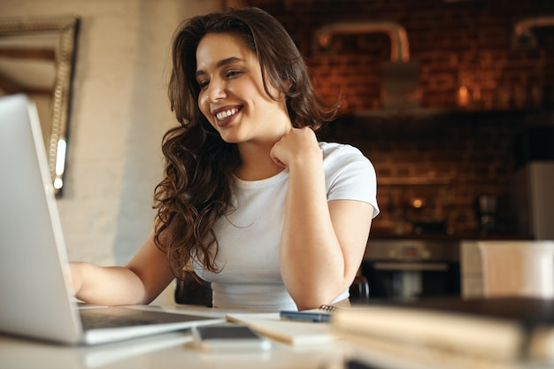 Joyful young female having break while working from home, sitting at desk in front of open laptop