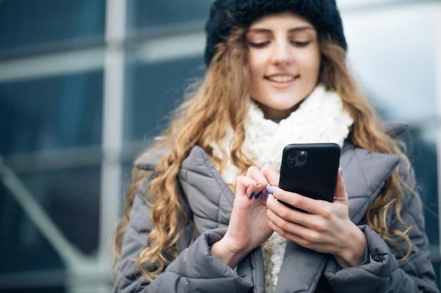 屋外のスマートフォンでタイピングとスクロールの機嫌が良い若い女性。