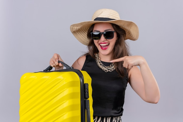 Joyful young female traveler wearing black undershirt in hat in glasses holding suitcase and points to suitcase on white wall