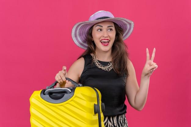 Gioiosa giovane viaggiatrice che indossa la maglietta nera in cappello che tiene la valigia che mostra il gesto di pace sulla parete rossa